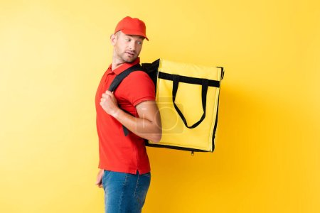 delivery man carrying and looking at backpack on yellow