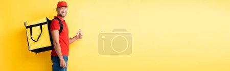 Photo pour Livreur joyeux portant sac à dos avec ordre et montrant pouce vers le haut sur jaune, bannière - image libre de droit