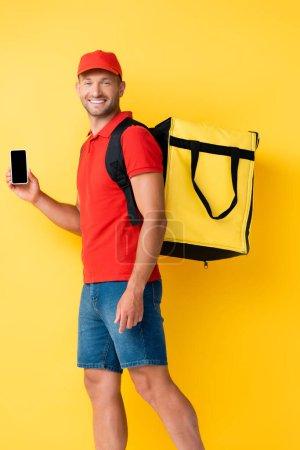 Photo pour Livreur joyeux portant sac à dos et tenant smartphone avec écran blanc sur jaune - image libre de droit
