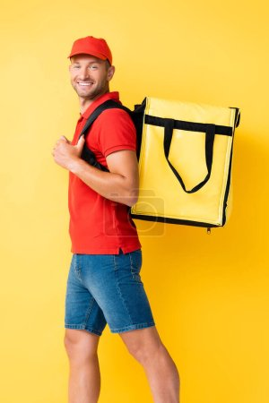 Photo for Cheerful delivery man carrying backpack with order on yellow - Royalty Free Image