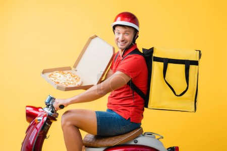 happy delivery man with backpack riding red scooter and holding pizza in carton box on yellow