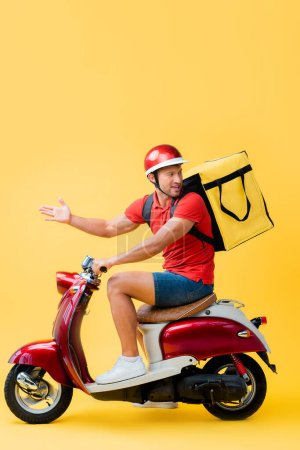 displeased delivery man with backpack gesturing while riding scooter on yellow