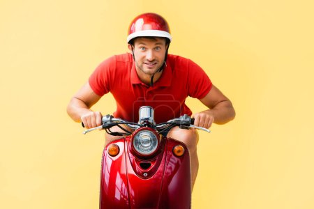 excited man in helmet riding red scooter on yellow