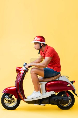 Photo for Side view of concentrated man in helmet riding red scooter on yellow - Royalty Free Image