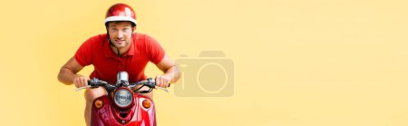 excited man in helmet riding red scooter isolated on yellow, banner