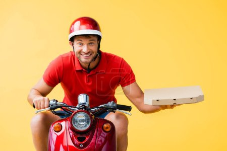 cheerful delivery man in helmet riding red scooter and holding pizza box isolated on yellow