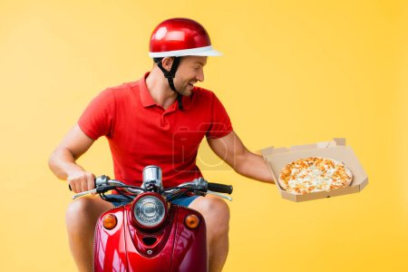 Photo for Happy delivery man in helmet riding red scooter and holding pizza in carton box isolated on yellow - Royalty Free Image