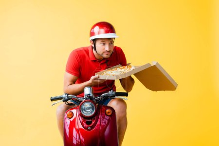 delivery man in helmet riding red scooter and smelling pizza in carton box on yellow