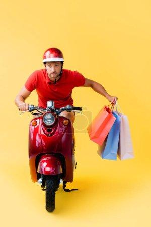 Photo pour Livreur dans un casque scooter d'équitation et portant des sacs à provisions sur jaune - image libre de droit