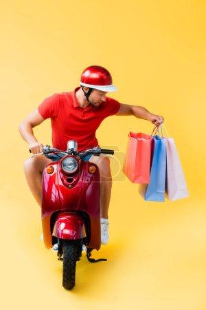 Photo pour Livreur en scooter d'équitation casque et à la recherche de sacs à provisions sur jaune - image libre de droit