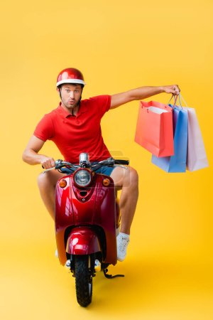 surprised delivery man in helmet riding scooter and holding shopping bags on yellow