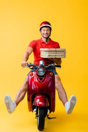 smiling delivery man in helmet riding scooter and holding carton pizza boxes on yellow