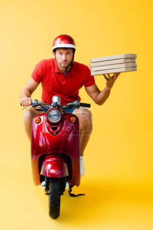focused delivery man in helmet riding scooter and holding carton pizza boxes on yellow