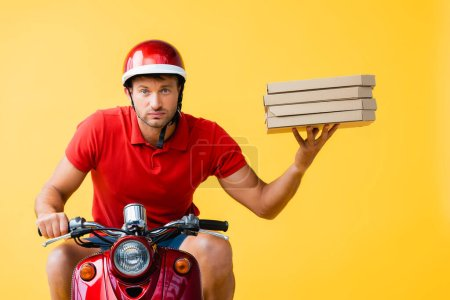 serious delivery man in helmet riding scooter and holding carton pizza boxes on yellow