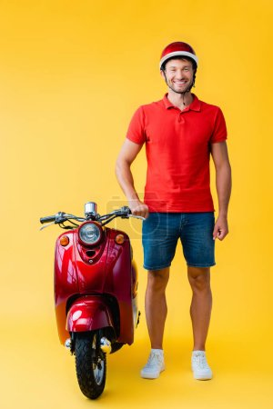full length of happy man in helmet standing near red scooter on yellow