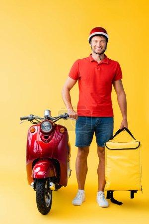 Photo pour Pleine longueur de livreur joyeux avec sac à dos debout près de scooter rouge sur jaune - image libre de droit