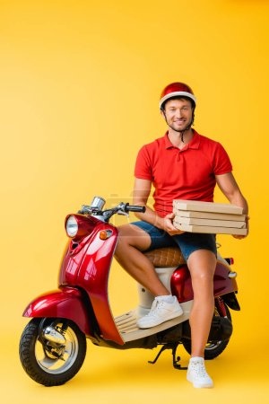 happy delivery man in helmet holding pizza boxes while sitting on scooter on yellow