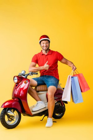 Photo for Happy delivery man in helmet sitting on scooter and holding shopping bags while showing thumb up on yellow - Royalty Free Image