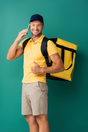 Photo for Cheerful delivery man carrying yellow backpack and talking on smartphone on blue - Royalty Free Image