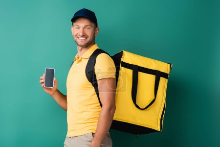Photo for Cheerful delivery man carrying yellow backpack and holding smartphone with blank screen on blue - Royalty Free Image