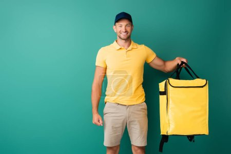 Photo for Cheerful delivery man carrying yellow backpack and smiling on blue - Royalty Free Image