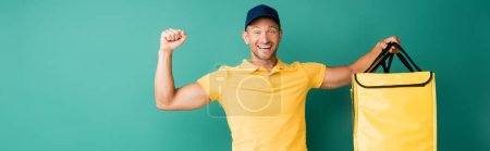 Photo for Excited delivery man carrying yellow backpack on blue, banner - Royalty Free Image