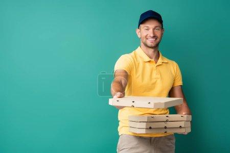 Photo pour Livreur heureux avec main tendue tenant boîtes à pizza sur bleu - image libre de droit