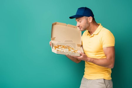pleased delivery man smelling tasty pizza in box on blue