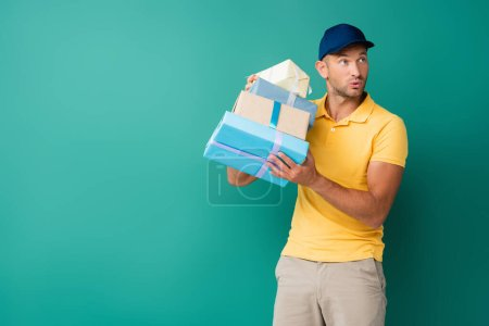 Photo for Curious delivery man in cap holding wrapped presents on blue - Royalty Free Image