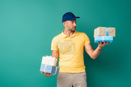 delivery man in cap holding wrapped presents on blue