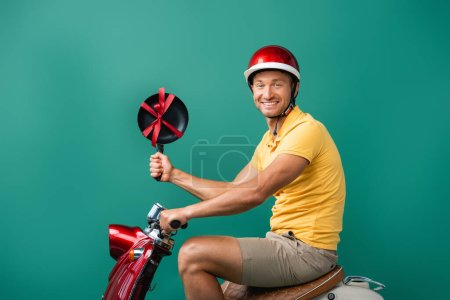 cheerful delivery man in helmet riding motorbike and holding frying pan with ribbon on blue