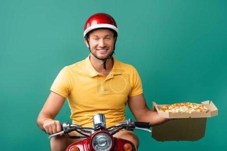 Photo pour Livreur souriant dans un casque scooter d'équitation tout en tenant une délicieuse pizza en boîte sur bleu - image libre de droit