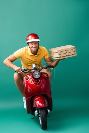 delivery man in helmet biting lips while riding scooter while holding pizza boxes on blue