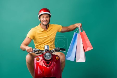 happy delivery man in helmet riding scooter while holding shopping bags on blue