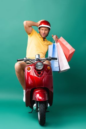 Photo for Shocked delivery man in helmet riding scooter while holding shopping bags on blue - Royalty Free Image