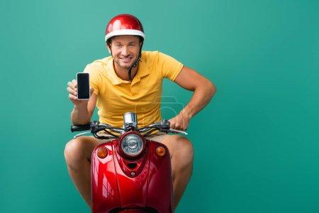 Photo pour Livreur gai dans le scooter d'équitation casque tout en tenant smartphone avec écran blanc sur bleu - image libre de droit