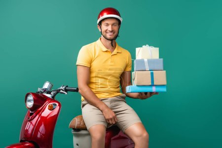 happy delivery man in helmet holding wrapped presents near scooter on blue
