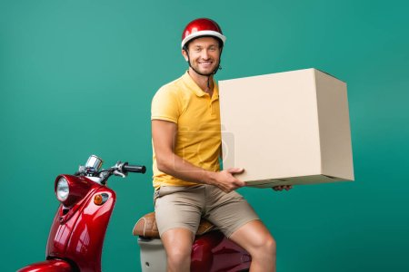 happy delivery man in helmet holding big carton box near scooter on blue