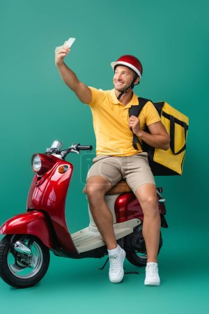 cheerful deliver man with backpack taking selfie near scooter on blue