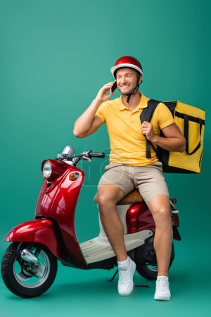cheerful delivery man with backpack talking on smartphone near scooter on blue