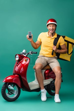 Photo for Excited delivery man with backpack holding smartphone with blank screen near scooter on blue - Royalty Free Image