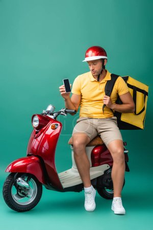 sad delivery man with backpack holding smartphone with blank screen near scooter on blue
