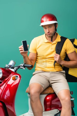 Photo pour Bouleversé livreur avec sac à dos tenant smartphone avec écran vide près de scooter sur bleu - image libre de droit