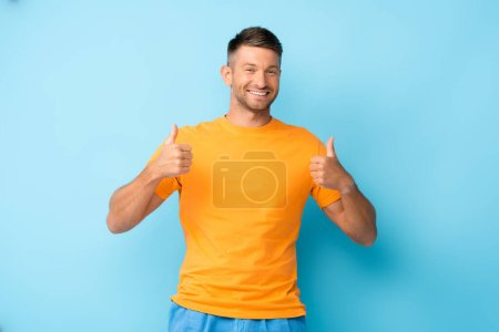 Photo for Happy man in yellow t-shirt showing thumbs up on blue - Royalty Free Image