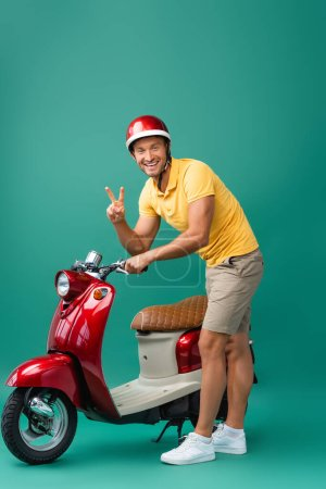 happy delivery man in helmet standing near red scooter and showing peace sign on blue