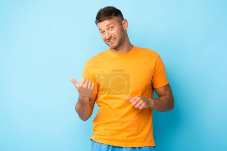 cheerful man in yellow t-shirt pointing with thumbs on blue