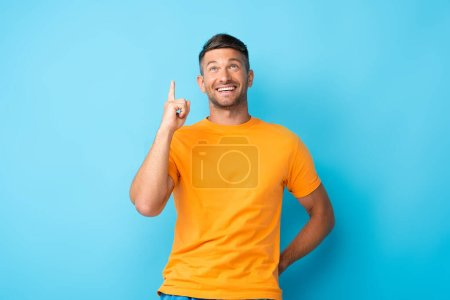 cheerful man in yellow t-shirt pointing with finger while looking up on blue