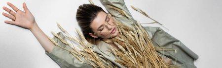 Hochwinkelaufnahme einer jungen trendigen Frau in Gläsern, die in der Nähe von Weizenstacheln auf weißem Grund liegt, Banner