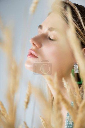 jeune femme aux yeux fermés près des épillets de blé au premier plan flou