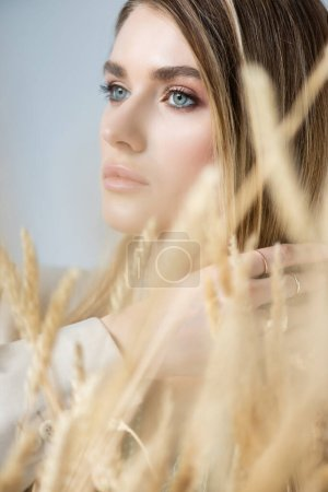 Photo for Young woman looking away near spikelets of wheat on blurred foreground - Royalty Free Image